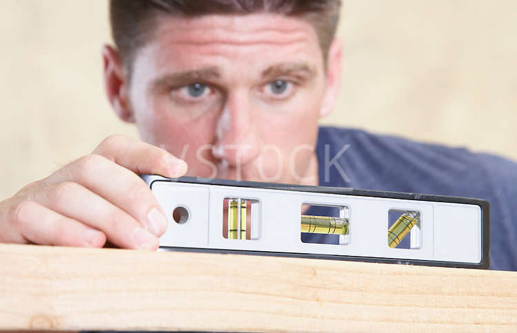 Man looking at level on piece of wood