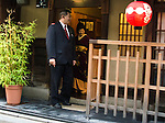 Driver stands outside ochaya waiting to take Geisha to the evening's appointment in Gion District of Kyoto
