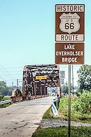 The Lake Overholser Bridge on Route 66 West of Oklahoma City.  Construction of the Overholser Bridge began in 1924 and the bridge opened for traffic in August of 1925.&nbsp; Accommodating a wide bed of 20 feet for traffic, the Overholser was no ordinary bridge.&nbsp; The engineers who designed it not only used the new steel truss technology, but also combined a variety of trusses in unusual ways.&nbsp; With both Parker through trusses and pony trusses, the 748-foot bridge is not only an unusual design, but a balanced and elegant one.<br /> <br /> For more than three decades the bridge served as a critical link for motorists traveling across the State and country.  &nbsp;By the 1950s, the bridge could not sustain this level of constant traffic.&nbsp; Heavily chromed cars with shapely fins had to sit too long at the bottleneck the bridge had become.&nbsp; In 1958, the Federal Government took action, replacing this segment of Route 66 with a new four-lane divided highway just to the north.