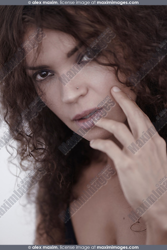 Closeup beauty portrait of a young caucasian brunette woman with a deep and piercing expressive look on her beautiful face with long curly dark brown hair