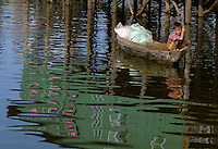 The Images from the Book Journey through Color and Time, 2006, Cambodia,A young boy in a traditional boat on the Tonle sap Water Village Tonle Sap lake