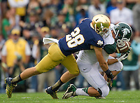 Safety Austin Collinsworth (28) tackles Michigan State Spartans tight end Josiah Price (82).