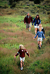 A family of five hike in a verdant meadow in Moraine Park, Rocky Mtn Nat'l Park, CO.