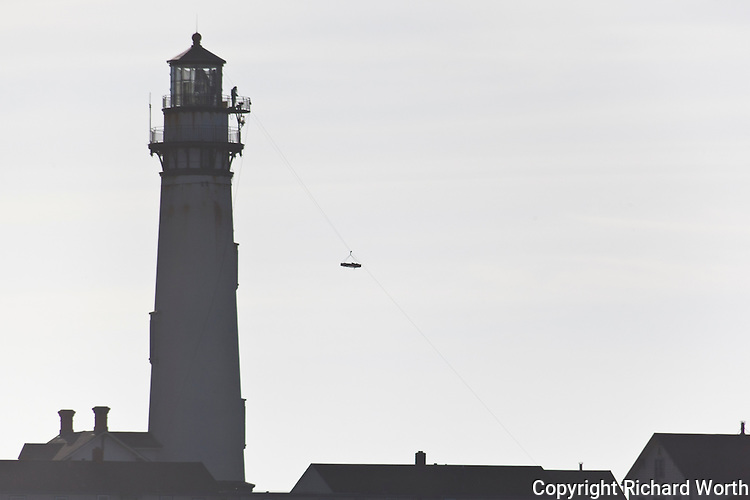Suspended in midair on a zipline stretched from the top of Pigeon Point Light Station, sections of the massive Fresnel lens are moved to the ground as part of the lighthouse restoration.