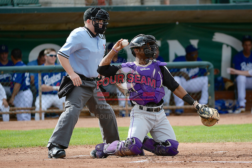 Jairo Rosario (12) of the Grand Junction Rockies in action against the Ogden Raptors with home plate umpire Marc Lindsey at Lindquist Field on September 8, 2013 in Ogden Utah.  (Stephen Smith/Four Seam Images)