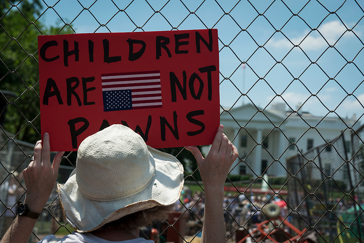 UNITED STATES – June 30: A woman holds an anti-Zero Tolerance policy sign at the Families Belong Together protest outside of the White House Saturday June 30, 2018.  (Photo By Sarah Silbiger/CQ Roll Call)