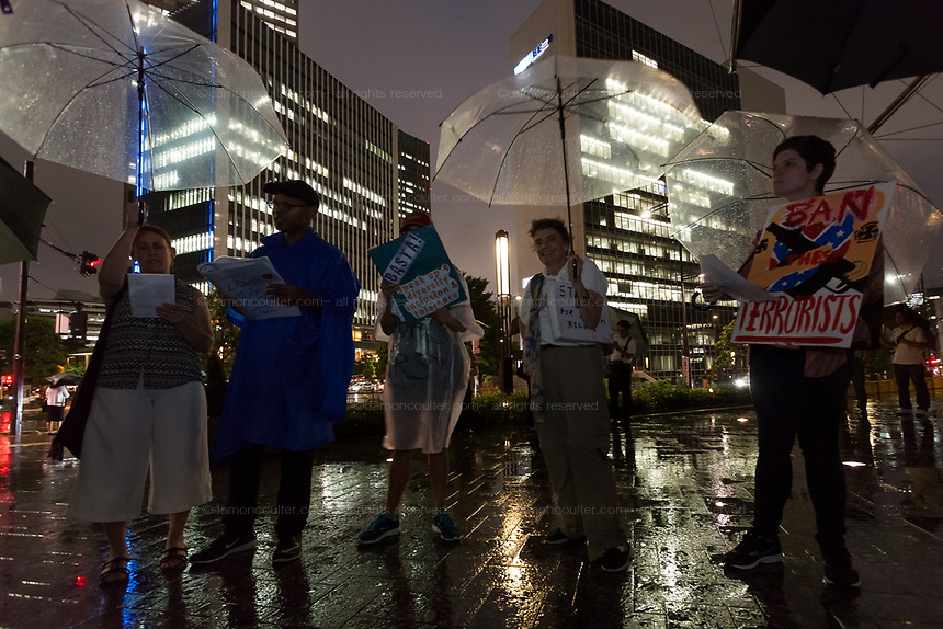 """American and Japanese  people at the  """"Enough is Enough"""" rally in Toranomon, Tokyo Japan, Tuesday August 15th 2017. Around 20 people gathered to take part in a global day of action demanding fairer policies in the United States that do not favour only the rich and do not remove human rights from ordinary people. A silent vigil was held for 30 minutes at 6pm so that the voices that could be heard after spoke louder. This is the closest it is possible to protest to the US embassy in Tokyo."""