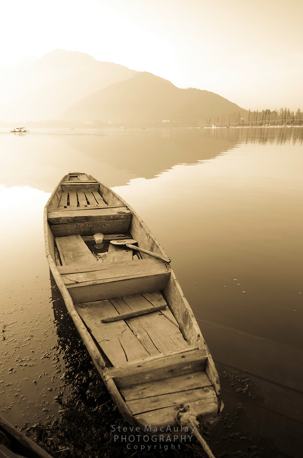 "Traditional ""shikara"" row boat at sunrise on the shore of Dal Lake, Srinagar, Kashmir, India."