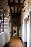 A glimpse down this corridor reveals the thickness of the stone walls in this Tudor house