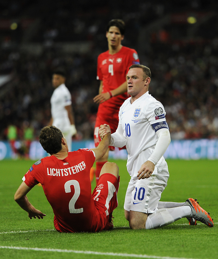 England&rsquo;s Wayne Rooney helps up Switzerland&rsquo;s Stephan Lichtsteiner after clashing in an aerial tussle<br /> <br /> Photographer Ashley Western/CameraSport<br /> <br /> International Football - UEFA EURO 2016 - UEFA European Championship Qualifying Group E - England v Switzerland - Tuesday 8th September 2015 - Wembley Stadium - London<br /> <br /> &copy; CameraSport - 43 Linden Ave. Countesthorpe. Leicester. England. LE8 5PG - Tel: +44 (0) 116 277 4147 - admin@camerasport.com - www.camerasport.com
