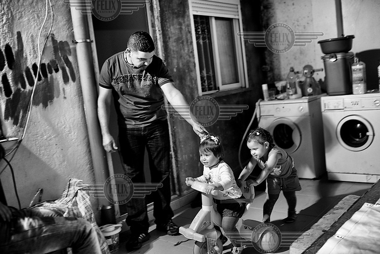 Edward Hernandez plays with his children in his flat, the night before their eviction. At the last the eviction was postponed due to the support of PAH (Mortgage Victims Platform) activists who confronted police, bank and court officials who had come to carry out the eviction.