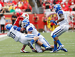 UK sophomore linebacker Tyler Brause (10) and senior defensive end Taylor Wyndham tackle UL junior runningback Senorise Perry during the first half of the UK vs. UL football game at Papa John's Cardinal Stadium in Louisville, Ky., on Sunday, September 2, 2012. Photo by Tessa Lighty | Staff