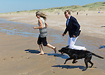 King Willem-Alexander of the Netherlands (L) and his wife Queen Maxima (R) play  with their dog during a photo session on the beach near Wassenaar, the Netherlands, July 10, 2015. © Michael Kooren