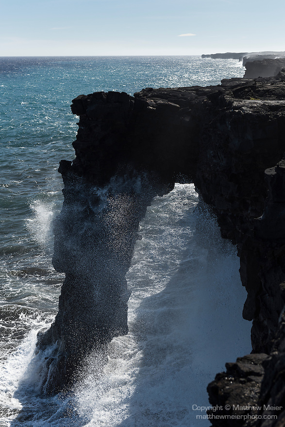 Hawai'i Volcanoes National Park, Big Island of Hawaii, Hawaii; large waves crashing into the rocks and splashing in front of the opening of the Holei Sea Arch at the end of the Chain of Craters Road