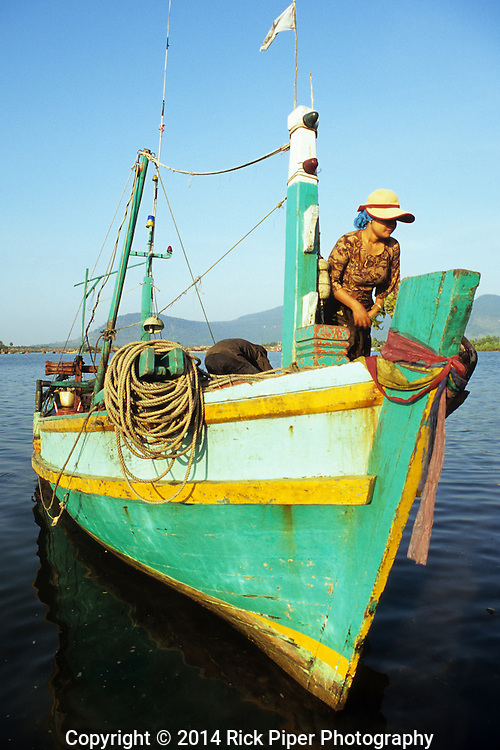 Cham woman on a colourful fishing boat, bringing in the nights catch, at dawn on the Sanke river, Kampot, Cambodia.