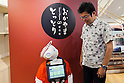 A customer greets to the humanoid robot Pepper who debuted as a new member of staff at the ''Tottori Okayama Shimbashi-kan'' store on July 1, 2015, Tokyo, Japan. The robot developed by SoftBank Corp. is programmed to interact with people and it is claimed that it can provide reception services in commercial establishments. Pepper will introduce the store's products and services to customers as a special employee for two days. The Tottori Okayama Shimbashi-kan sells unique food and traditional handicraft products from Tottori and Okayama prefectures in western Japan. (Photo by Rodrigo Reyes Marin/AFLO)