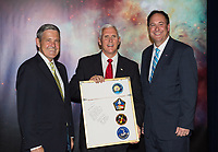 In this photo released by the National Aeronautics and Space Administration (NASA) United States Vice President Mike Pence receives a commemorative montage from Kennedy Space Center (KSC) Director, Robert Cabana, left, and Acting NASA Administrator, Robert Lightfoot, right, including stickers on the back from all of Cabana's missions, Thursday, July 6, 2017, in the green room at KSC in Cape Canaveral, Florida. Vice President Mike Pence is scheduled to speak at the event to highlight innovations made in America and tour some of the public/private partnership work that is helping to transform the center into a multi-user spaceport. Photo Credit: Aubrey Gemignani/NASA/CNP/AdMedia