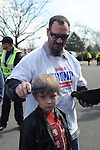 """A supporter of Republican presidential frontrunner Donald Trump combs his son's hair as they wait in line to enter before a town hall at the Holiday Inn Express in Janesville, Wisconsin on March 29, 2016.  Father told son, """"Let me comb your hair son before we meet the next president of the United States."""""""