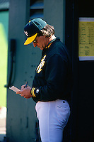 OAKLAND, CA - Manager Tony La Russa of the Oakland Athletics looks at his lineup card in the dugout during a game at the Oakland Coliseum in Oakland, California in 1994. (Photo by Brad Mangin)