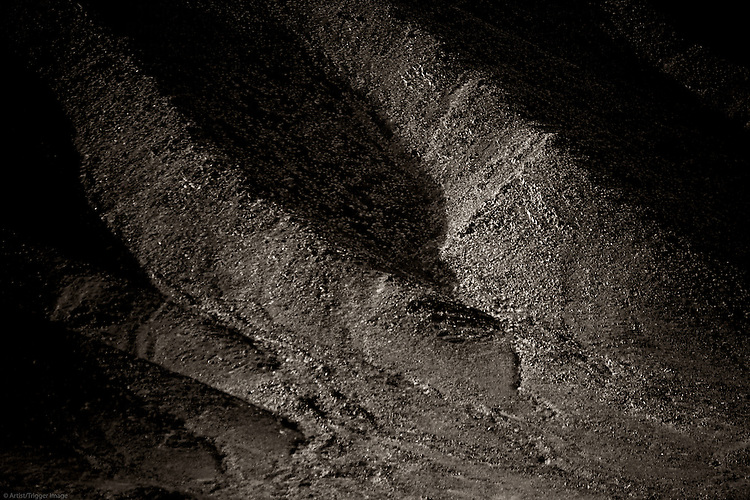 A dark mountainside of rugged and striking rock formations.