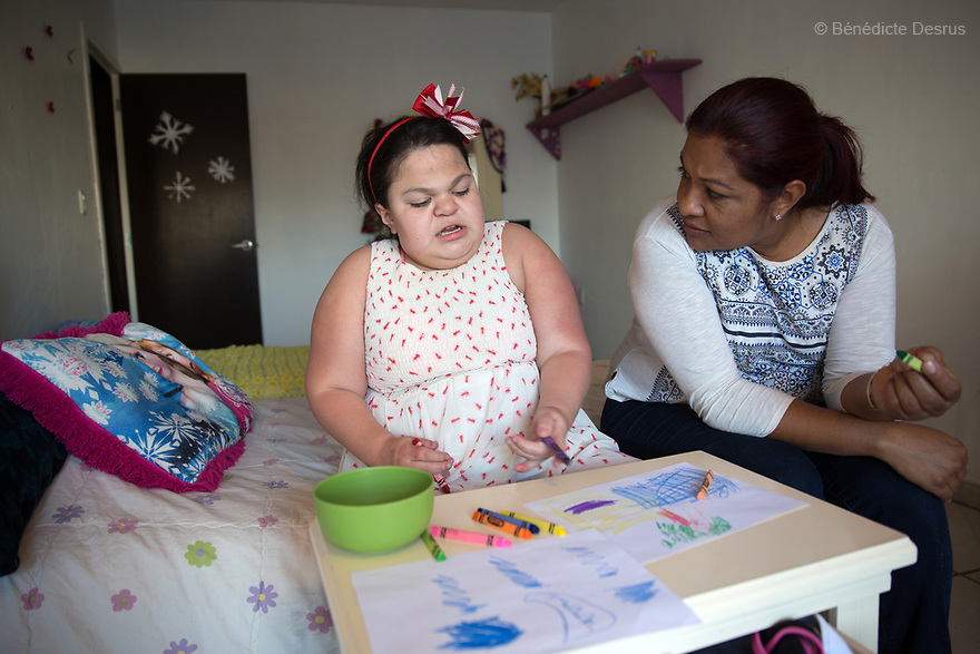 """Ana Ximena Navarro (L) is pictured drawing with her aunt Gabriela Rios Ballesteros (R), at her home in Guadalajara, Mexico on February 22, 2017. Ximena was diagnosed as an infant with Hurler syndrome. Hurler syndrome is the most severe form of mucopolysaccharidosis type 1 (MPS1), a rare lysosomal storage disease, characterized by skeletal abnormalities, cognitive impairment, heart disease, respiratory problems, enlarged liver and spleen, characteristic facies and reduced life expectancy. Ximena was being given enzyme replacement therapy (ERT) when she was 19 months old, and she was suddenly able to eat and sleep. She is now 12, and has normal hormonal development for her age, although some mental delay, according to her father. """"Without the treatment, she would have died from all the complications — untreated, children have a very bad quality of life and typically die before they are seven"""", her father says. Photo credit: Bénédicte Desrus"""
