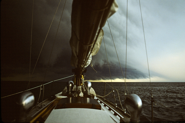 A shelf cloud moves across the bow of a classic sailboat on Lake Erie.