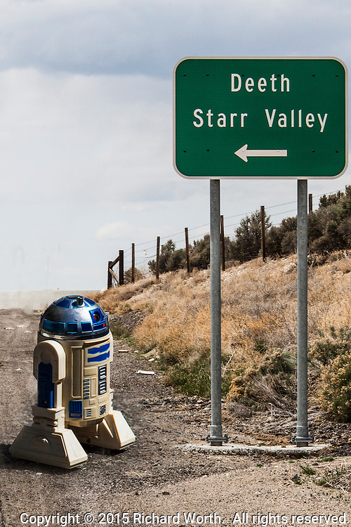 "A roadsign along Intersate 80 In Nevada pointing the way to ""Deeth"" and ""Starr Valley"" has been combined in photo software with a toy R2D2 robot."