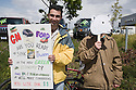 Two protestors with a sign and polar bear mask at a Step It Up 2007 protest rally. They are protesting for increased vehicle fuel efficiency to help to reduce CO2 emissions in relation to climate change. The sign addresses General Motors (GM) and Ford which are American automakers, reading 'GM, Ford Are You Ready to Sink or Swim in the New Green Economy?' San Rafael, California, USA