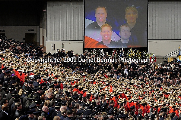 A picture of the four slain officers hangs over the crowd during a memorial service in Tacoma, WA Tuesday December 8, 2009. The memorial brought an estimated 20,000 police officers and community members to the area.