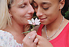 Portrait of lesbian couple standing together holding flower,