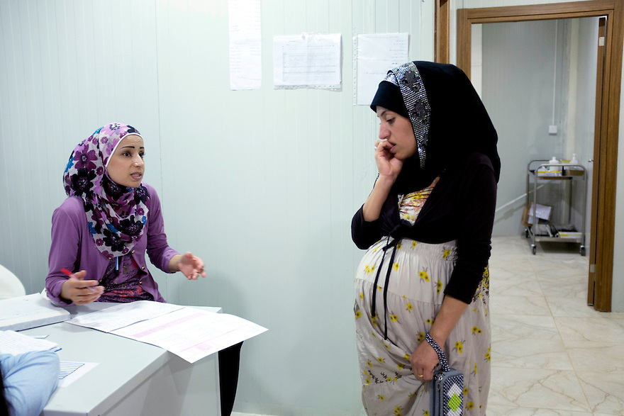 Syrian midwife Abla Ali, left, speaks with a patient at the MSF-run maternity clinic at Domiz refugee camp in Iraqi Kurdistan. PHOTO BY JODI HILTON