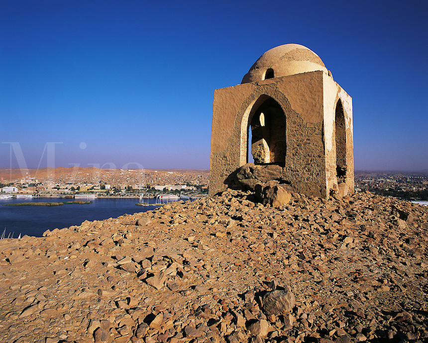 Simple Islamic shrine on a hilltop above the Nile at Aswan, Egypt. The NIle and city of Aswan visible behind