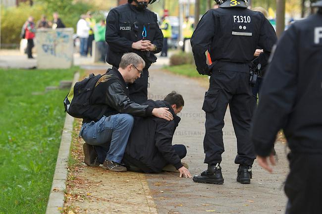 Rechte Buerger aus Berlin Hellersdorf demonstrieren am Samstag den 26. Oktober 2013 gemeinsam mit Neonazis der NPD und der Partei &quot;Die Rechte&quot; unter dem Motto: &quot;Tag der Meinungsfreiheit&quot; gegen ein Fluechtlingsheim in Berlin-Hellersdorf.<br />Gegendemonstranten blockierten die Demonstration mit einer Sitzblockade, so dass die Rechten ihren Marsch abbrechen mussten.<br />Im Anschluss meldeten die Neonazis eine weitere Demonstration an. Auch hier versuchten Gegendemonstranten den Aufmarsch mit Sitzblockaden zu verhindern, wurden jedoch von der Polizei mit Gewalt von der Strasse gebracht und eingekesselt.<br />Hier: Beim Versuch die Sitzblockade zu raeumen wurde dem Demonstranten durch die festnehmenden Beamten mit einen  sog. &quot;Schmerzgriff&quot; der Kehlkopf gequetscht so dass er kollabierte und kurzzeitig ohnmaechtig wurde. Die Baemten haben sich nur neben den Mann gestellt und ein Passant leistete Hilfe bis ein Krankenwagen kam.<br />26.10.2013, Berlin<br />Copyright: Christian-Ditsch.de<br />[Inhaltsveraendernde Manipulation des Fotos nur nach ausdruecklicher Genehmigung des Fotografen. Vereinbarungen ueber Abtretung von Persoenlichkeitsrechten/Model Release der abgebildeten Person/Personen liegen nicht vor. NO MODEL RELEASE! Don't publish without copyright Christian Ditsch/version-foto.de, Veroeffentlichung nur mit Fotografennennung, sowie gegen Honorar, MwSt. und Beleg. Konto:, I N G - D i B a, IBAN DE58500105175400192269, BIC INGDDEFFXXX, Kontakt: post@christian-ditsch.de.<br />Urhebervermerk wird gemaess Paragraph 13 UHG verlangt.]