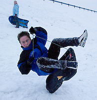 A young boy goes airborne at the bottom of a snow-covered slope on the facing edge of a reservoir dam in Columbus, Ohio, Thursday, December 23, 2004. A winter storm covered central Ohio with as much as a foot of snow and an inch of ice forcing school and business closings. Photo by Gary Gardiner, The Eyepush Network