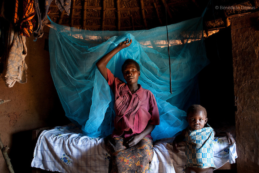 15 april 2010  Busagazi, Uganda - Janet Mutesi and her son sit on their bed with a mosquito net used for preventing malaria. Malaria is a mosquito-borne infectious disease. The disease kills over a million people in the world every year, mostly children and pregnant women. Malaria transmission can be reduced preventing mosquito bites by using mosquito nets and insect repellents, or by mosquito-control measures such as spraying insecticides inside houses and draining standing water where mosquitoes lay their eggs. Photo credit: Benedicte Desrus