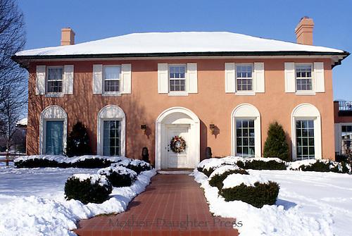 Italian stucco house design in winter with Christmas wreath on door and brick walkway welcoming guests