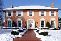 Italian stucco house design in winter with Christmas wreath on door and brick walkway welcoming guests