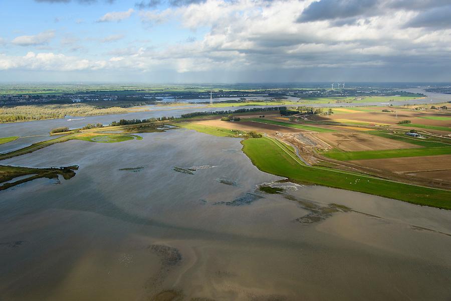 Nederland, Noord-Brabant, Werkendam, 23-10-2013; Ruimte voor de Rivier project Ontpoldering Noordwaard, rivier de Nieuwe Merwede aan de horizon. Het deel links is reeds ontpolderd, rechts het gedeelte in ontwikkeling waar boerderijen en particuliere huizen op nieuw opgeworpen terpen gebouwd worden.<br /> Voor dit project worden delen van de polder ontpolderd en de dijken worden verlegd en/of verlaagd waardoor bij hoogwater het rivierwater ook door de polder sneller weg kan stromen richting zee. Gevolg van de ingrepen is ook dat de waterstand verder stroomopwaarts zal dalen.<br /> As part of the program Ruimte voor de rivier (Room for the River)  this polder Noordwaard is not a polder any longer by managed retreat, but a freshwater tidal reserve.<br /> luchtfoto (toeslag op standard tarieven);<br /> aerial photo (additional fee required);<br /> copyright foto/photo Siebe Swart