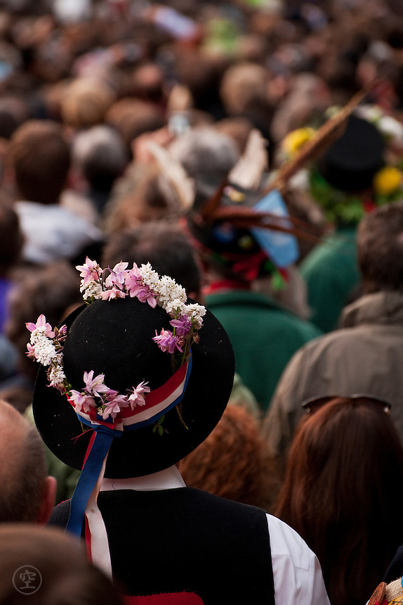 Morris dancers stand among the crowds at dawn on May Morning, Oxford, to listen to the choir sing from Magdalen Tower.