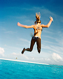FIJI, Northern Lau Islands, a young woman jumps off of a the top of a yacht into the South Pacific Ocean