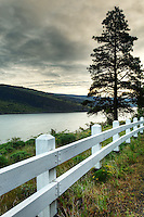 Morning over the Columbia River with white wooden guard rail along edge of Mosier Twin Tunnels Trail, Mosier, Oregon, USA