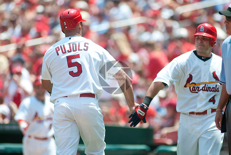 10 July 2011            St. Louis Cardinals first baseman Albert Pujols (5) slaps hands with St. Louis Cardinals catcher Yadier Molina (4) after he scores early in the game. The St. Louis Cardinals defeated the Arizona Diamondbacks 4-2 in the final game of a four-game series on Sunday July 10, 2011 at Busch Stadium in downtown St. Louis.