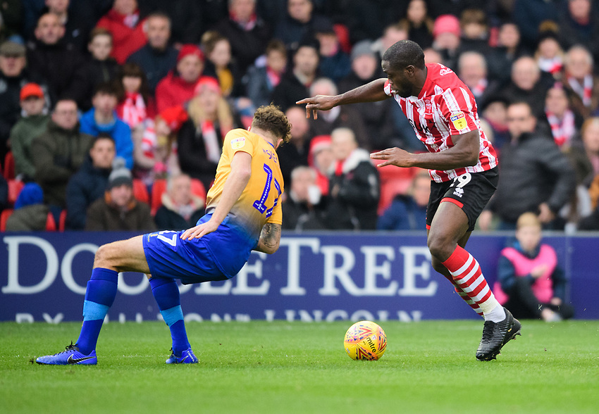 Lincoln City's John Akinde vies for possession with Mansfield Town's Ryan Sweeney<br /> <br /> Photographer Chris Vaughan/CameraSport<br /> <br /> The EFL Sky Bet League Two - Lincoln City v Mansfield Town - Saturday 24th November 2018 - Sincil Bank - Lincoln<br /> <br /> World Copyright © 2018 CameraSport. All rights reserved. 43 Linden Ave. Countesthorpe. Leicester. England. LE8 5PG - Tel: +44 (0) 116 277 4147 - admin@camerasport.com - www.camerasport.com