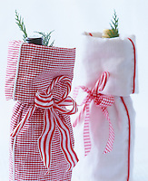 Bottles of wine presented in red and white fabric holders tied with ribbon and decorated with candy canes make festive Christmas gifts