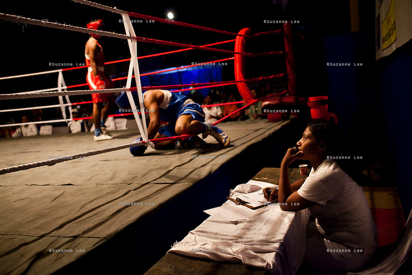Razia Shabnam looks on at a fallen boxer as she judges a bout at an all-India invitational boxing competition in the neighbouring town of Burnpur, Calcutta, West Bengal, India. Razia Shabnam, 28, was one of the first women boxers in Kolkata. She was also the first woman in her community to go to college. She is now a coach and one of only three international female boxing referees in India. Photo by Suzanne Lee for Panos London