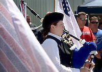 NWA Democrat-Gazette/BEN GOFF @NWABENGOFF<br /> Kara Mason plays 'Amazing Grace' on bagpipes flanked by memorial flags bearing the names of those who died in the Sept. 11, 2001 attacks on Saturday Sept. 12, 2015 during the Sheep Dog Impact Assistance annual Patriot Day event at Bentonville Municipal Airport. The event honored the victims of the Sept. 11, 2001 terrorist attacks and offered visitors a chance to get an up close look at military and emergency response vehicles.