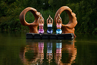 BNPS.co.uk (01202 558833)<br /> Pic: ZacharyCulpin/BNPS<br /> <br /> and relax....<br /> <br /> A yoga class by a takes place on the water in front of the sculpture 'Search for Enlightenment' by sculptor and owner of Sculpture by the Lakes, Simon Gudgeon. <br /> Pictured: (from left) Gail Taylor, Martha Manson and Pip Taverner.<br /> <br /> Sculpture by the Lakes near Dorchester in Dorset will be hosting a brand new 3 day festival, 'Wellbeing by the Lakes'. The event 'aims to explore explore what it means to be mindful and how to live well in our fast-paced modern world' it will run from Thursday 19th September – Saturday 21st September 2019
