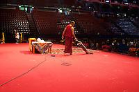Milano: un monaco tibetano passa l'aspirapolvere sul palco dove si terrà l'incontro con il Dalai Lama Tenzin Gyatso..Milan: a Tibetan monaco cleans the stage, before the speech of the Dalai Lama Tenzin Gyatso