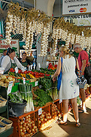 Woman and man shopping at a vegetable vendor's stall in the Jean Talon public market or Marche Jean Talon, Montreal, Quebec, Canada
