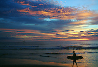 A surfer carries his surfboard along the beach as the sun sets in Playa Tamarindo, Costa Rica, August 15, 2003.